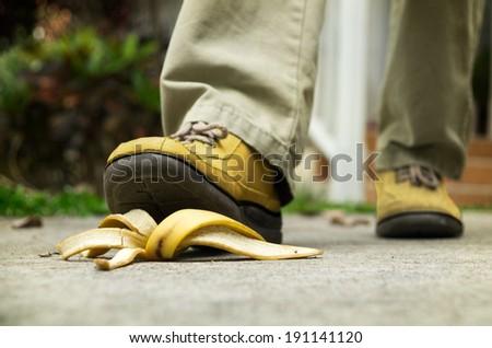 man stepping on banana peel - stock photo
