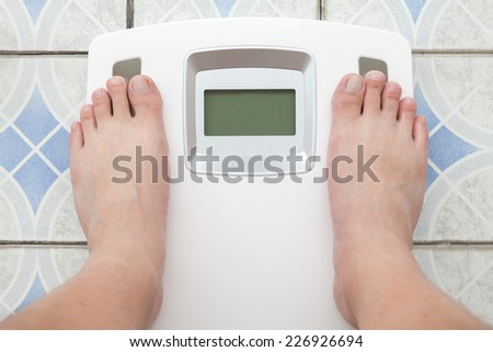 Man steps on digital weight machine - stock photo