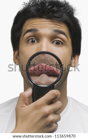 Man sticking his tongue out in front of a magnifying glass - stock photo