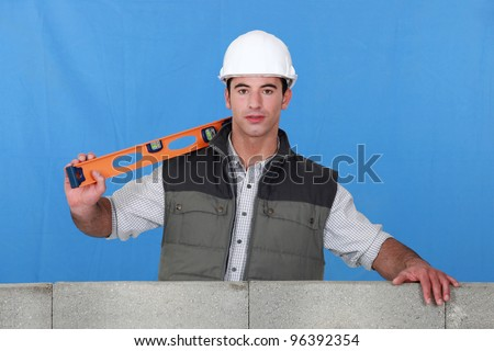 Man stood by wall with spirit-level - stock photo