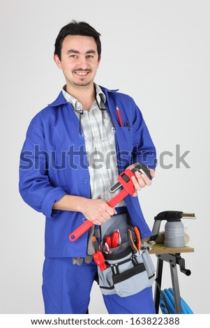 Man stood with wrench and blow torch - stock photo