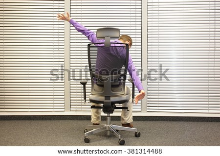man  stretching arms sitting on chair in office  -  back view - stock photo