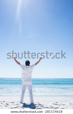 Man stretching his arms in front of the sea at the beach - stock photo