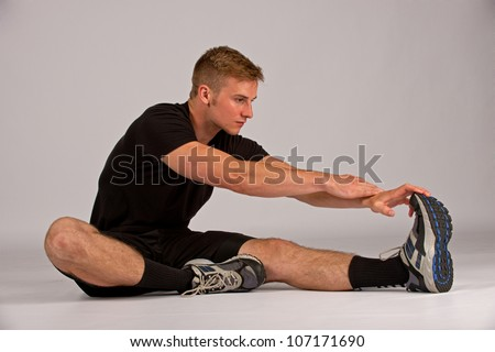 Man stretching his legs as he prepares for a run and daily exercise. - stock photo
