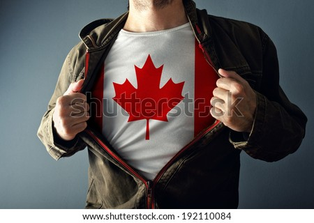 Man stretching jacket to reveal shirt with Canada flag printed. Concept of patriotism and national team supporting. - stock photo
