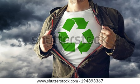 Man stretching jacket to reveal shirt with recycle symbol printed. Concept of environmental consciousness and natural preservation.