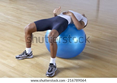 Man stretching on a fitness ball.