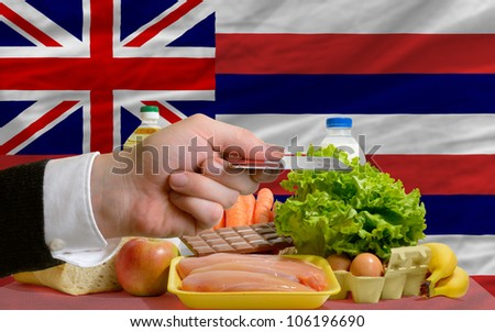man stretching out credit card to buy food in front of complete wavy american state flag of hawaii