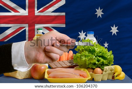 man stretching out credit card to buy food in front of complete wavy national flag of australia