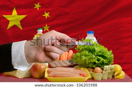man stretching out credit card to buy food in front of complete wavy national flag of china - stock photo