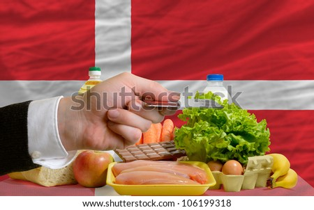 man stretching out credit card to buy food in front of complete wavy national flag of denmark - stock photo