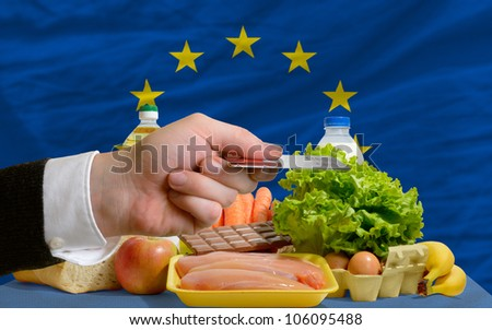 man stretching out credit card to buy food in front of complete wavy national flag of europe - stock photo