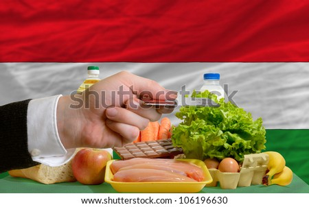 man stretching out credit card to buy food in front of complete wavy national flag of hungary - stock photo