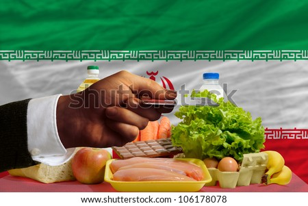 man stretching out credit card to buy food in front of complete wavy national flag of iran - stock photo