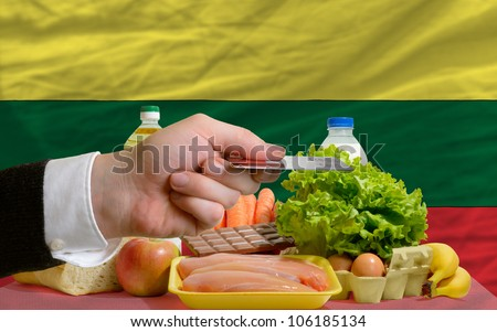 man stretching out credit card to buy food in front of complete wavy national flag of lithuania - stock photo