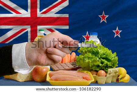 man stretching out credit card to buy food in front of complete wavy national flag of new zealand