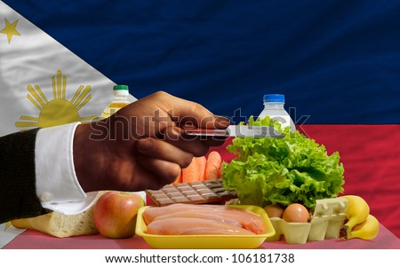 man stretching out credit card to buy food in front of complete wavy national flag of philippines - stock photo