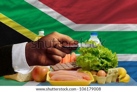man stretching out credit card to buy food in front of complete wavy national flag of south africa - stock photo