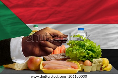 man stretching out credit card to buy food in front of complete wavy national flag of sudan - stock photo