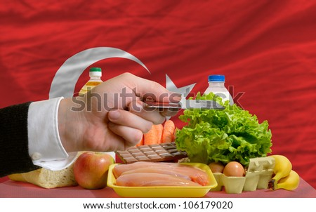 man stretching out credit card to buy food in front of complete wavy national flag of turkey - stock photo