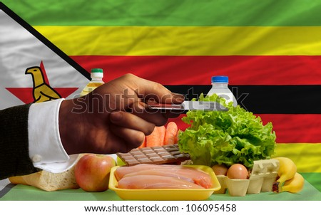 man stretching out credit card to buy food in front of complete wavy national flag of zimbabwe - stock photo