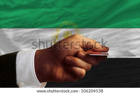 man stretching out credit card to buy goods in front of complete wavy national flag of afghanistan - stock photo