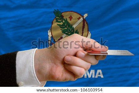 man stretching out credit card to buy goods in front of complete wavy national flag of american state of oklahoma - stock photo