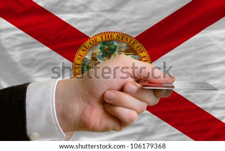 man stretching out credit card to buy goods in front of complete wavy national flag of american state of florida - stock photo