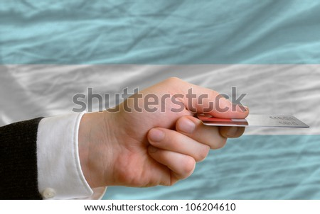 man stretching out credit card to buy goods in front of complete wavy national flag of argentina - stock photo