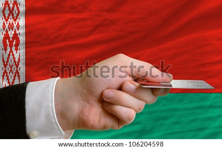 man stretching out credit card to buy goods in front of complete wavy national flag of belarus - stock photo