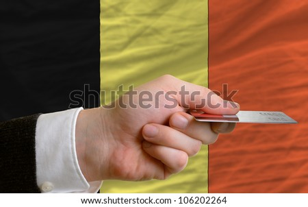 man stretching out credit card to buy goods in front of complete wavy national flag of belgium - stock photo