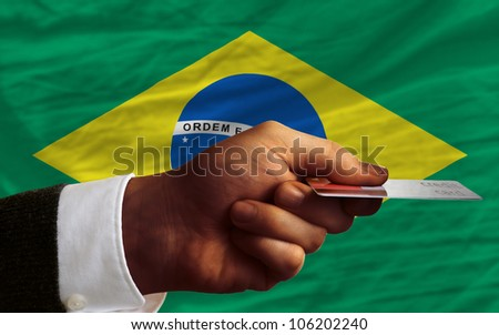 man stretching out credit card to buy goods in front of complete wavy national flag of brazil