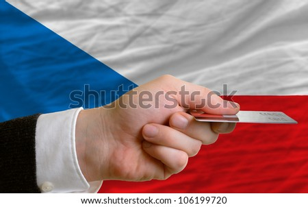 man stretching out credit card to buy goods in front of complete wavy national flag of czech - stock photo