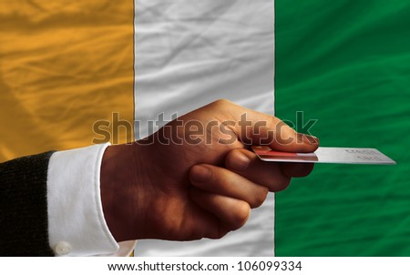 man stretching out credit card to buy goods in front of complete wavy national flag of ivory coast - stock photo