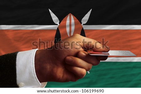 man stretching out credit card to buy goods in front of complete wavy national flag of kenya - stock photo