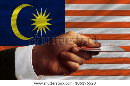 man stretching out credit card to buy goods in front of complete wavy national flag of malaysia - stock photo