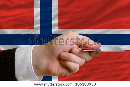 man stretching out credit card to buy goods in front of complete wavy national flag of norway - stock photo