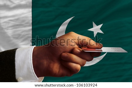 man stretching out credit card to buy goods in front of complete wavy national flag of pakistan - stock photo