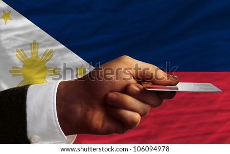 man stretching out credit card to buy goods in front of complete wavy national flag of philippines - stock photo