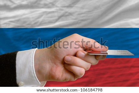man stretching out credit card to buy goods in front of complete wavy national flag of russia - stock photo