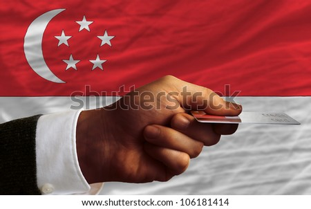man stretching out credit card to buy goods in front of complete wavy national flag of singapore - stock photo