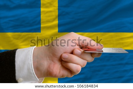 man stretching out credit card to buy goods in front of complete wavy national flag of sweden - stock photo