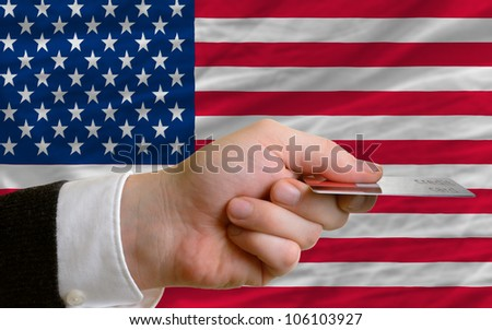 man stretching out credit card to buy goods in front of complete wavy national flag of united states of america