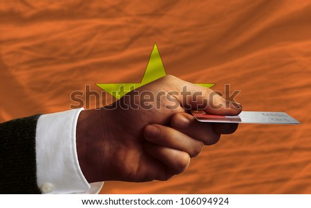 man stretching out credit card to buy goods in front of complete wavy national flag of vietnam - stock photo