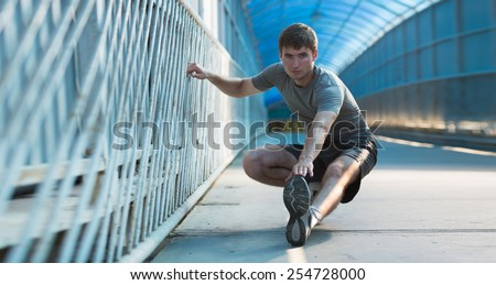Man stretching outdoors in city - stock photo