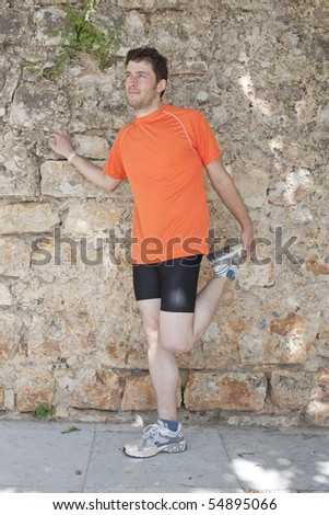 Man stretching to start running by a stone wall - stock photo