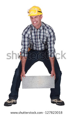 Man struggling to carry building block - stock photo