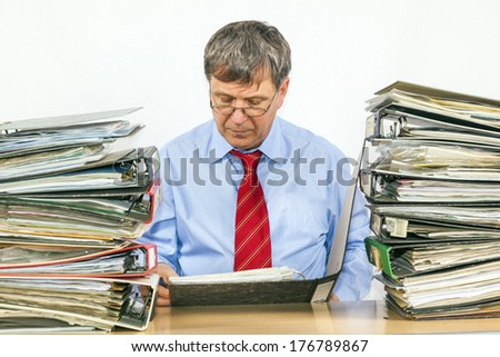 man studies many folder with files at his desk in the office
