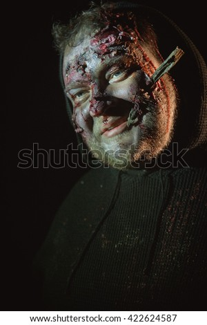 Man styled like a zombie grins