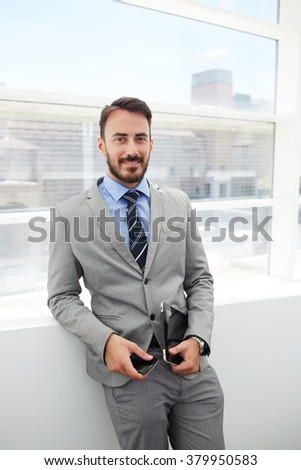 Man successful leader holding cell telephone and touch pad while smiling for camera during work break, male manager in good mood standing with digital tablet and smart phone in hallway of big company